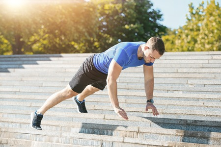 Fit man doing exercises outdoors at park Stock Photo
