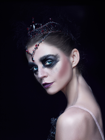 Portrait of the ballerina in the role of a black swan on black background Stock Photo