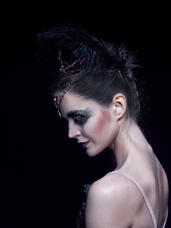 Portrait of the ballerina in the role of a black swan on black background Stock fotó