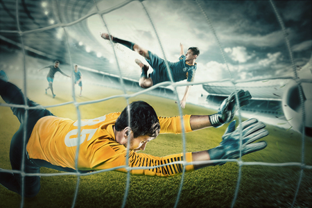 Goalkeeper in gates jumping to catching ball Stock Photo - 80683828