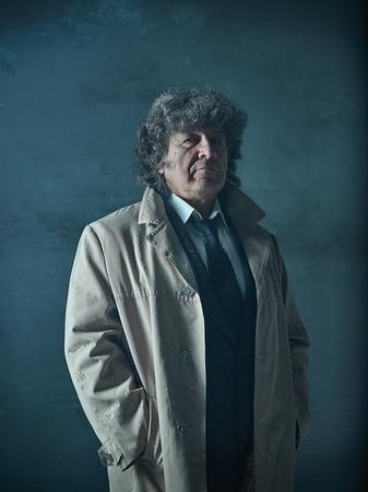 探偵または灰色のスタジオの背景にマフィアのボスとして年配の男性