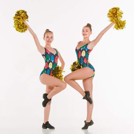 black cheerleader: The two of teen cheerleaders posing at white studio