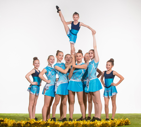 black cheerleader: The group of teen cheerleaders posing at white studio