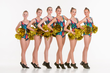 The group of teen cheerleaders posing at white studio