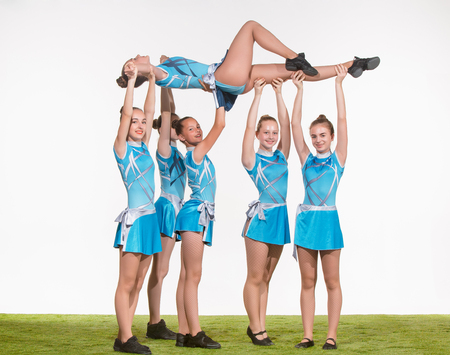 The group of teen cheerleaders posing at white studio