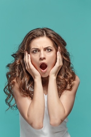 astonishment: Portrait of young woman with shocked facial expression