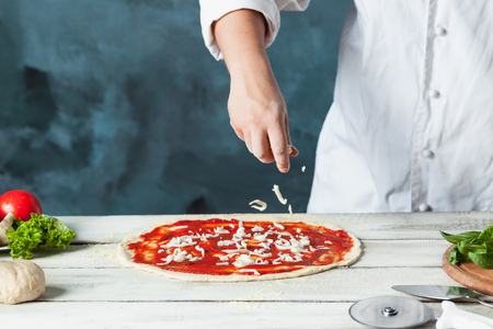 Closeup hand of chef baker in white uniform making pizza at kitchen Imagens