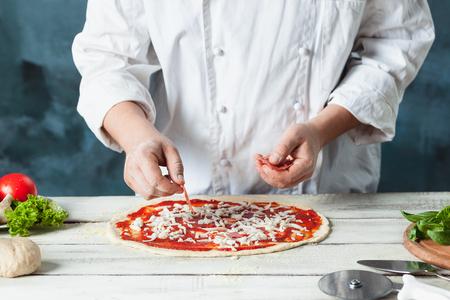 gros plan de boulanger boulanger dans le blanc uniforme portant pizza à la cuisine