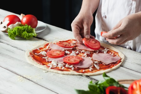 Closeup hand of chef baker in white uniform making pizza at kitchen Stock Photo