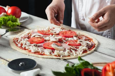白い制服を着てキッチンでピザを作るシェフのパン屋のクローズ アップ手