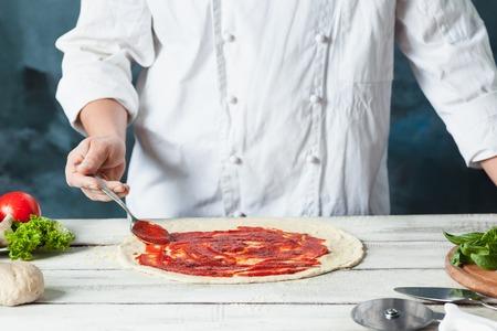 Closeup hand of chef baker in white uniform making pizza at kitchen Reklamní fotografie