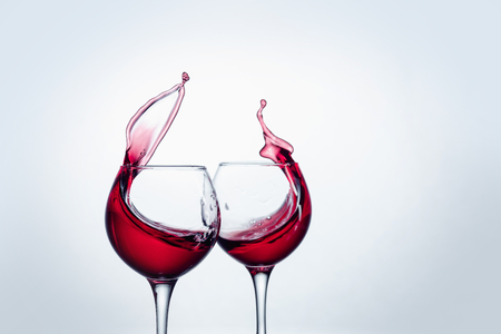 Two wine glasses in toasting gesture with big splashing.