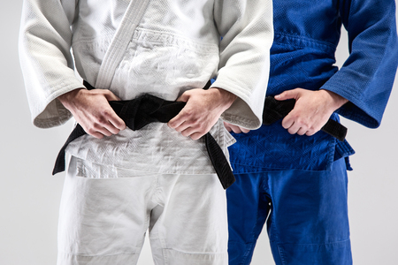 The two judokas fighters posing at studio Фото со стока