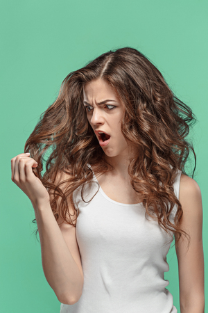 Frustrated young woman having a bad hair on blue Stok Fotoğraf