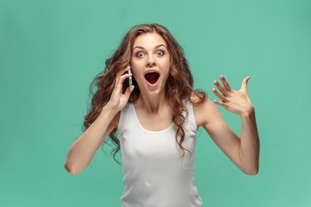 Geschokte vrouw die mobiele telefoon op groene achtergrond bekijkt