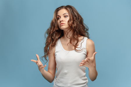 huffy: Portrait of an angry woman looking away on a blue background