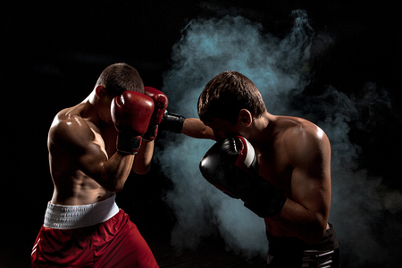 Two professional boxer boxing on black smoky background, Foto de archivo