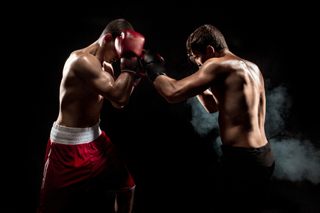 Two professional boxer boxing on black smoky background, Stock Photo