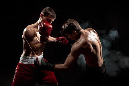 Dos boxeador boxeo profesional sobre fondo negro ahumado,