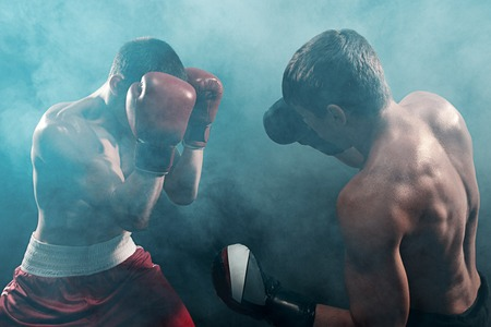 Two professional boxer boxing on black smoky background, Stock fotó