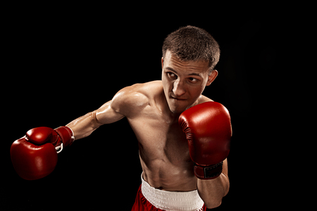 Male boxer boxing with dramatic edgy lighting in a dark studio
