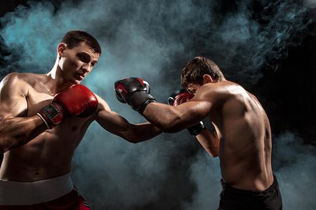 Two professional boxer boxing on black smoky background, Stok Fotoğraf