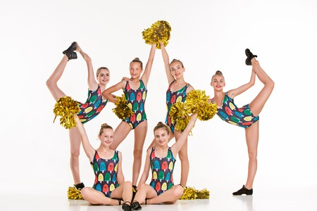 The group of teen cheerleaders posing at studio over white.