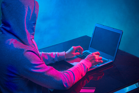 Hooded computer hacker stealing information with laptop Standard-Bild
