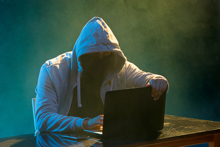Hooded computer hacker stealing information with laptop Imagens
