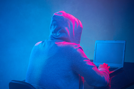 trojan: Hooded computer hacker stealing information with laptop Stock Photo