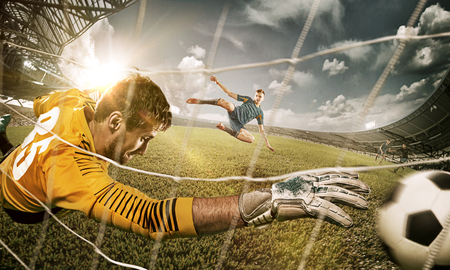 Goalkeeper in gates jumping to catching ball Foto de archivo