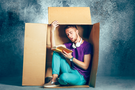 Introvert concept. Man sitting inside box and reading book Stock Photo