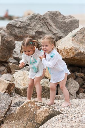 바다 해변에서 아이들. 돌과 바다 물에 대하여 서있는 쌍둥이. 스톡 콘텐츠