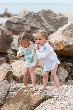 Children on the sea beach. Twins standing against stones and sea water. Banque d'images