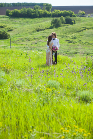 Just married loving couple in wedding dress on green field in a forest at summer 版權商用圖片