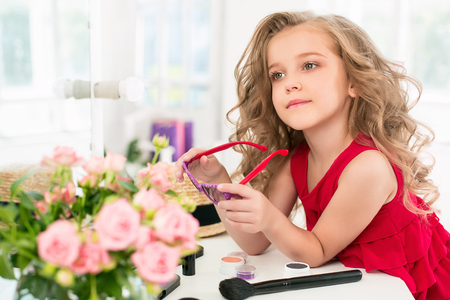Ein kleines Mädchen mit Kosmetika. Sie ist im Schlafzimmer der Mütter und sitzt nahe dem Spiegel. Standard-Bild - 83261807