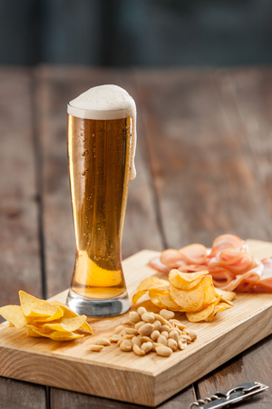 Beer glass and potato chips, pistachios isolated on a white