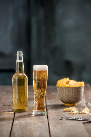 alcoholismo: Copa de cerveza y papas fritas, pistachos aislados en un blanco Foto de archivo