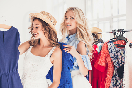 Image of pretty females looking a dress while choosing it. Concept of shopping Stock fotó
