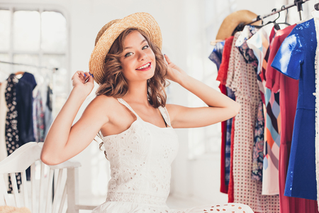 Attractive woman trying on a hat. Happy summer shopping. Stock Photo - 83363916