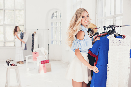 hangers: The young pretty girl choosing and trying on dresses at shop