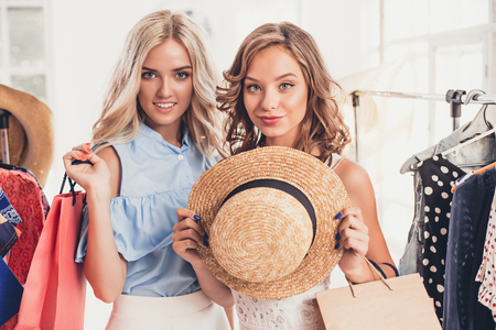 hangers: The two young pretty girls looking at dresses and try on it while choosing at shop