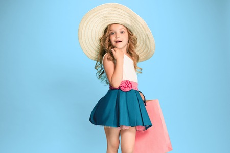 The cute little caucasian brunette girl in dress holding shopping bags Banque d'images