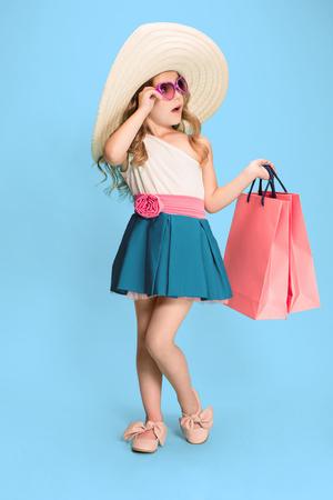 The cute little caucasian brunette girl in dress holding shopping bags Stock fotó