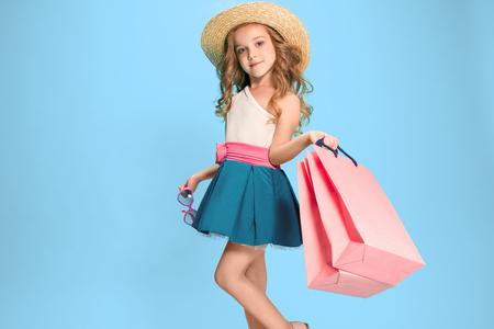 Het schattige kleine Kaukasische brunette meisje in jurk bedrijf boodschappentassen Stockfoto