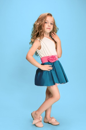 Full length of beautiful little girl in dress standing and posing over blue background Фото со стока - 83551365