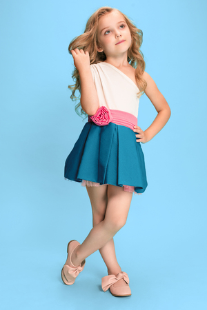 Full length of beautiful little girl in dress standing and posing over blue background