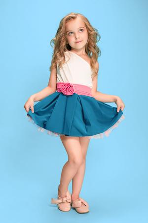 Longueur entière de belle petite fille en tenue debout et posant sur fond bleu Banque d'images - 83551367