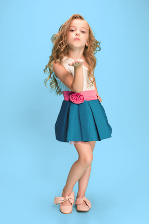 서서 파란색 배경 위에 포즈를 취하는 아름다운 소녀의 전체 길이 드레스 스톡 콘텐츠