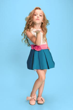 Pleine longueur de la belle petite fille en robe debout et posant sur fond bleu Banque d'images - 83551383